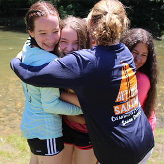 students hugging at camp